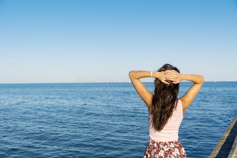 享受与开放胳膊的自由的妇女夏天在海滩 库存照片