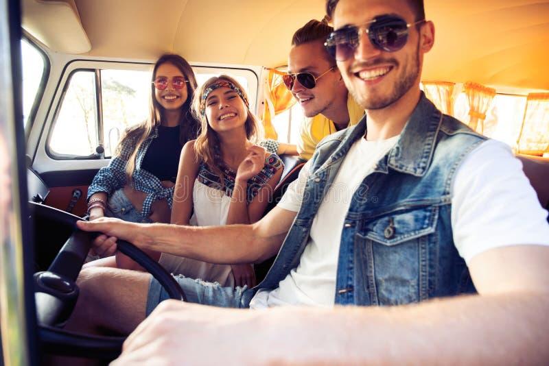 享受与朋友的巨大roadtrip 获得小组快乐的青年人乐趣,当坐在微型货车里面时 图库摄影