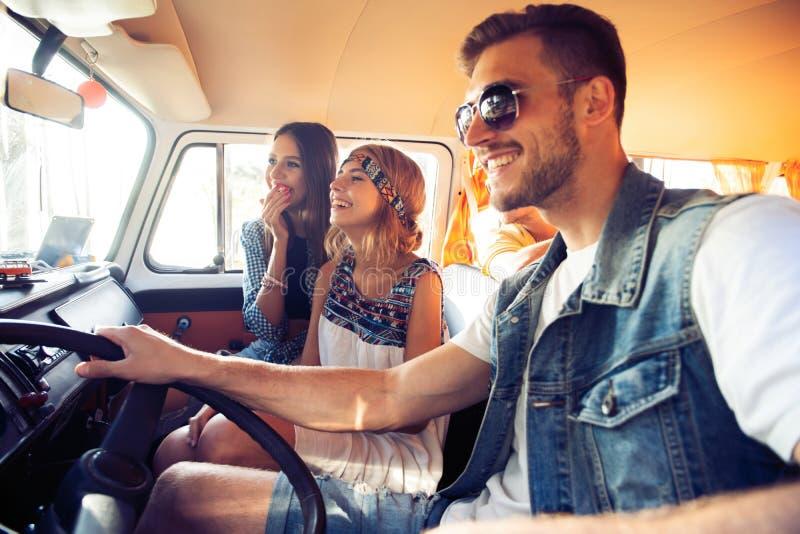 享受与朋友的巨大roadtrip 获得小组快乐的青年人乐趣,当坐在微型货车里面时 库存图片