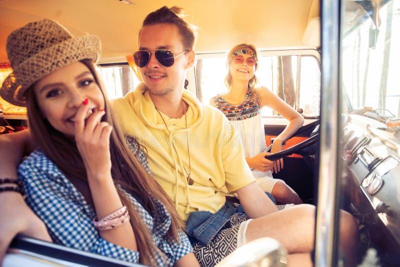 享受与朋友的巨大roadtrip 获得小组快乐的青年人乐趣,当坐在微型货车里面时 免版税图库摄影