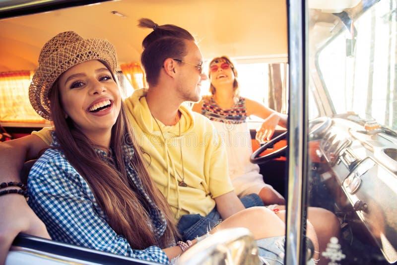 享受与朋友的巨大roadtrip 获得小组快乐的青年人乐趣,当坐在微型货车里面时 免版税库存图片