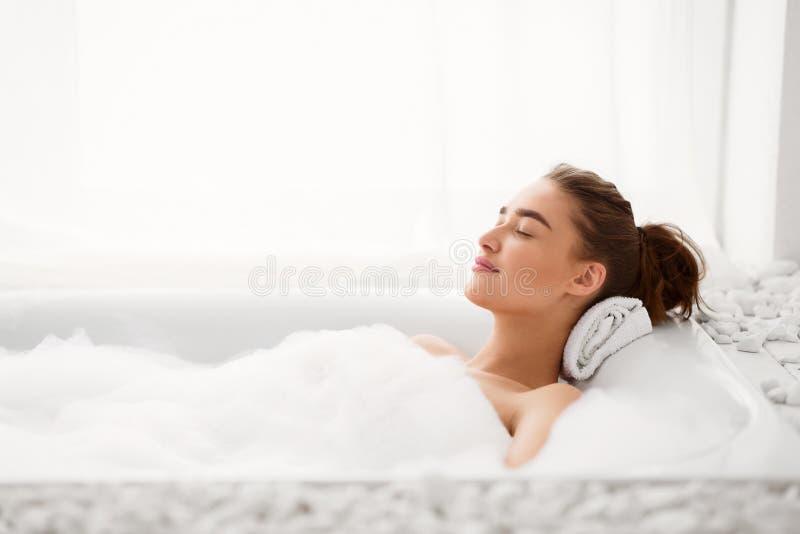 ( 享受与泡沫的妇女热水澡 库存图片