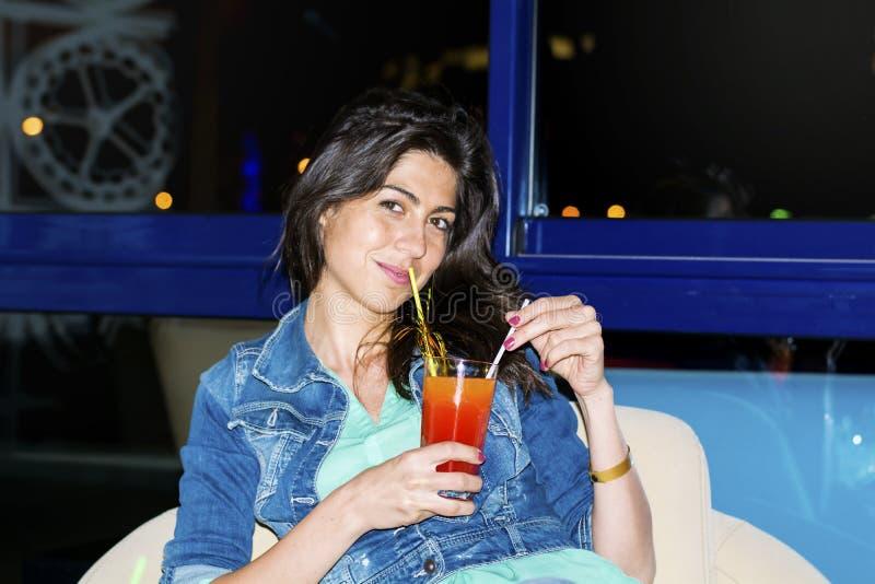 享受与红色酒精鸡尾酒的少妇暑假在手上 免版税库存图片