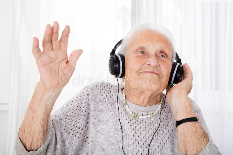 享受与耳机的资深妇女音乐 免版税库存图片