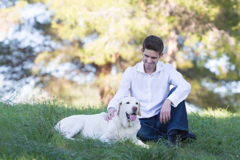 享受与他的拉布拉多狗的白种人人业余时间 库存照片