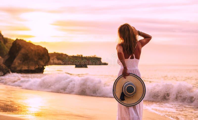 享受五颜六色的日落的妇女在海滩的晚上 库存图片