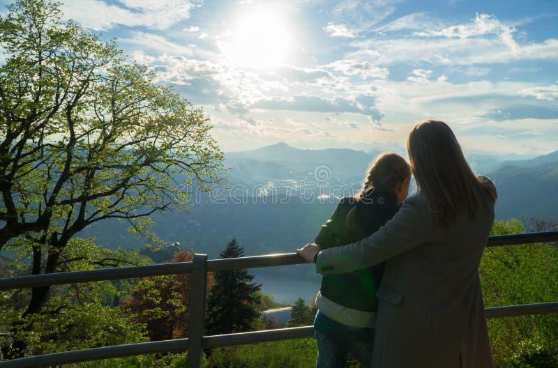 享受从山上面的妇女和她的女儿日出  库存图片