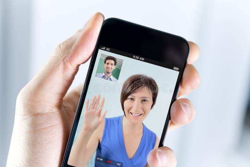 享受从smartphone的夫妇一种视频购买权 免版税图库摄影