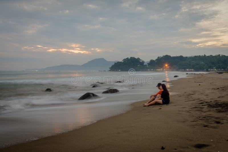 享受他们的在卡朗火山Hawu海滩,西爪哇省,印度尼西亚的愉快的夫妇片刻 库存照片
