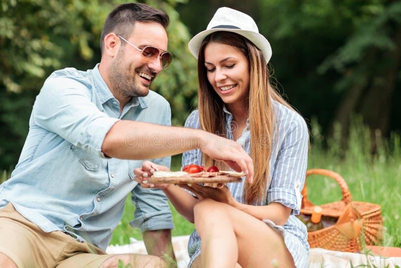 享受他们的时间的微笑的愉快的年轻夫妇在公园,有一顿偶然浪漫野餐 免版税图库摄影