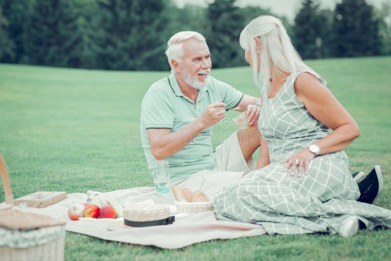 享受他们的浪漫野餐的宜人的年迈的夫妇 库存图片