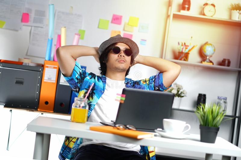 享受他的假日的时髦的年轻专家,当工作时 库存照片