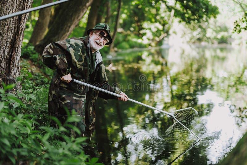 享受他钓鱼的周末的快乐的年迈的钓鱼者 免版税库存照片