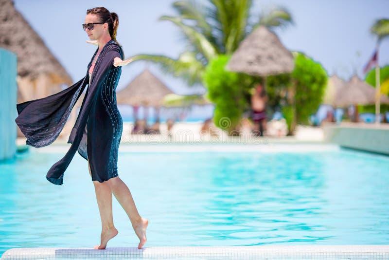 享受休息的年轻美丽的妇女在室外游泳池边缘 库存图片