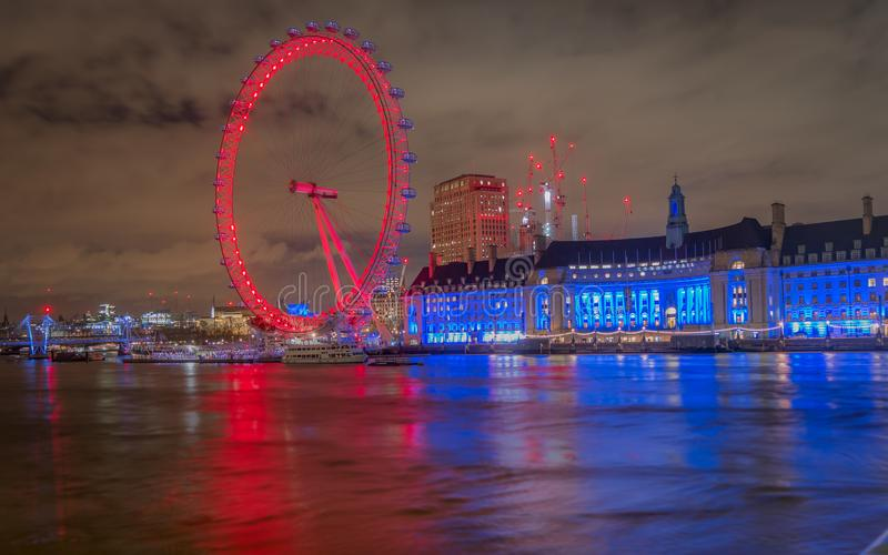 享受伦敦眼睛的一个可爱的看法点燃了与五颜六色的光在从威斯敏斯特桥梁的晚上 库存图片