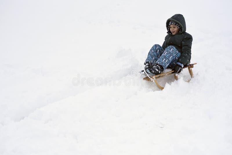 享受使用在雪橇乘驾的愉快的孩子 库存图片