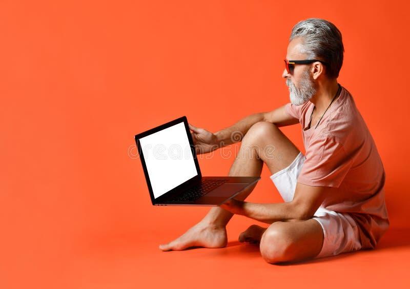 享受使用新的膝上型计算机的时髦领抚恤金者画象 免版税图库摄影