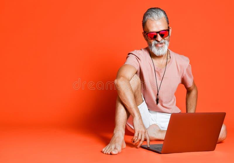 享受使用新的膝上型计算机的时髦领抚恤金者画象 图库摄影