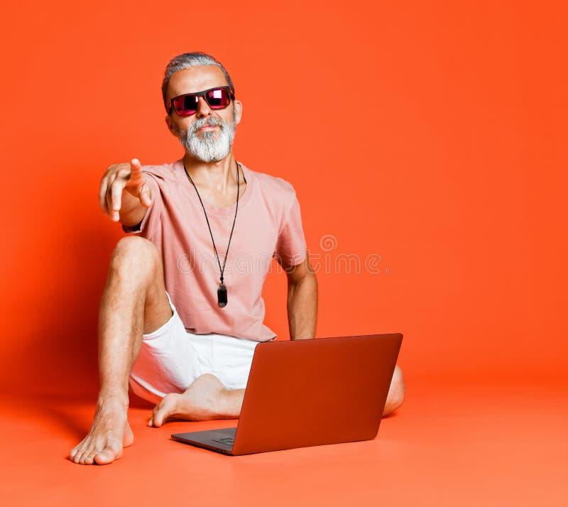 享受使用新的膝上型计算机的时髦领抚恤金者画象 库存图片
