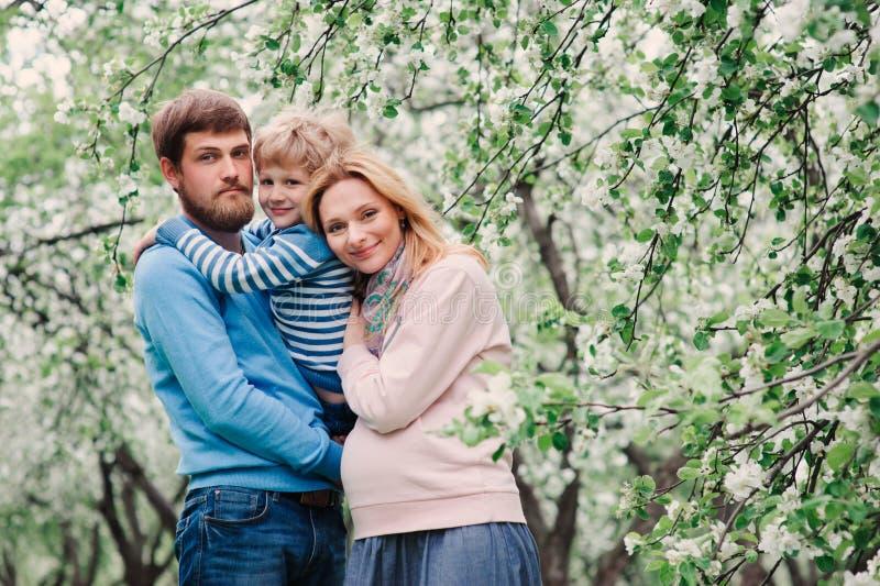 享受假日的愉快的家庭春天画象在开花的庭院里 免版税图库摄影