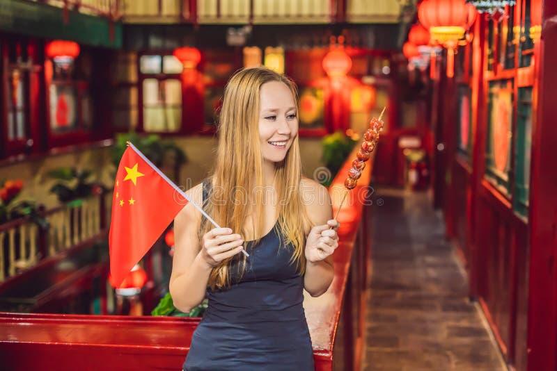 享受假期在中国 愉快的妇女游人有中国旗子的和用在a的传统中国脯 库存照片