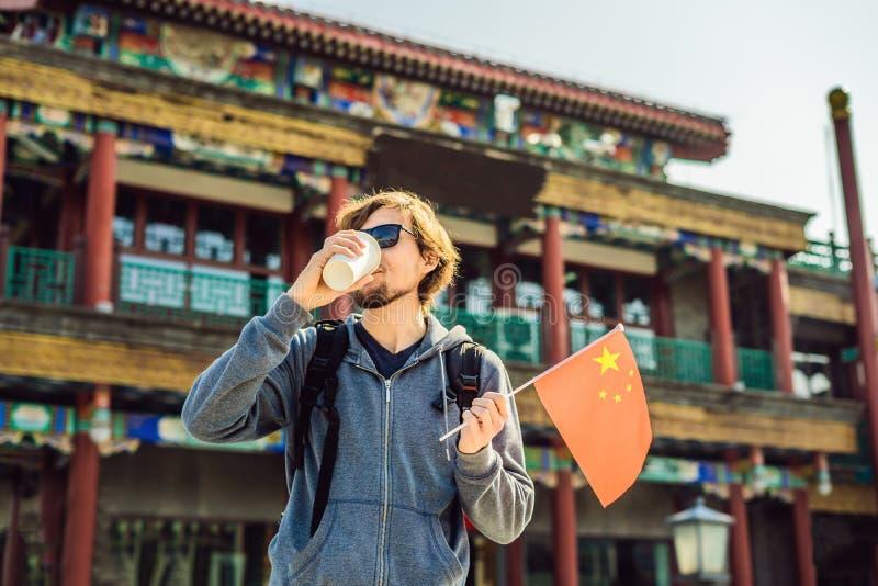享受假期在中国 有全国中国旗子的年轻人在老中国街道的背景 背景旅行的袋子护照白色 库存图片
