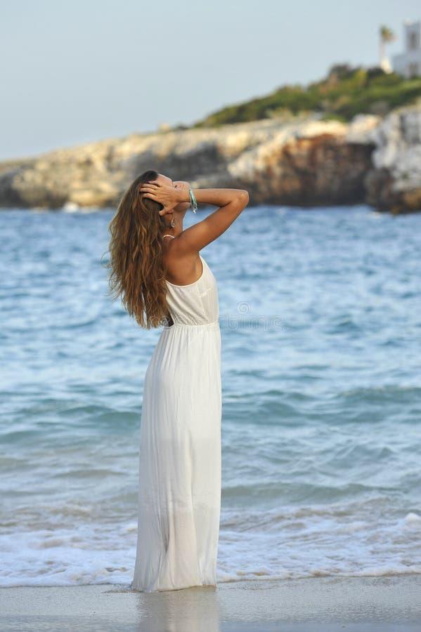 享受假期暑假的可爱和美丽的妇女在西班牙沿岸航行走在海滩的村庄 图库摄影