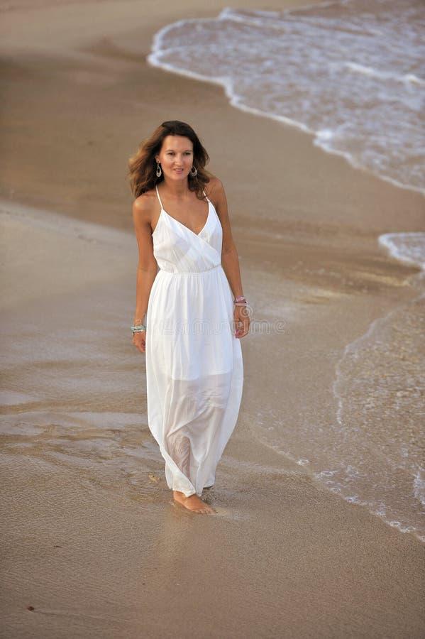 享受假期暑假的可爱和美丽的妇女在西班牙沿岸航行走在海滩的村庄 免版税库存照片
