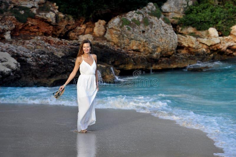 享受假期暑假的可爱和美丽的妇女在西班牙沿岸航行走在海滩的村庄 免版税图库摄影