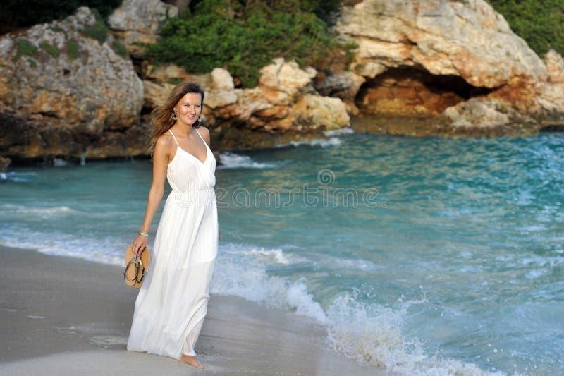 享受假期暑假的可爱和美丽的妇女在西班牙沿岸航行走在海滩的村庄 免版税库存图片