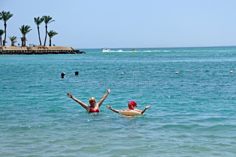 享受假期游泳的母亲和女儿在海 库存图片