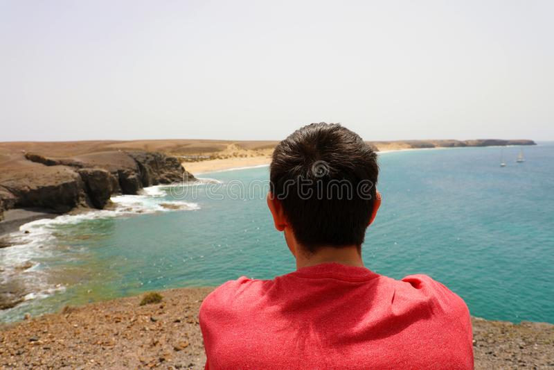 享受兰萨罗特岛风景的后面观点的一个坐的人在Playas de Papagayo,加那利群岛 免版税库存照片