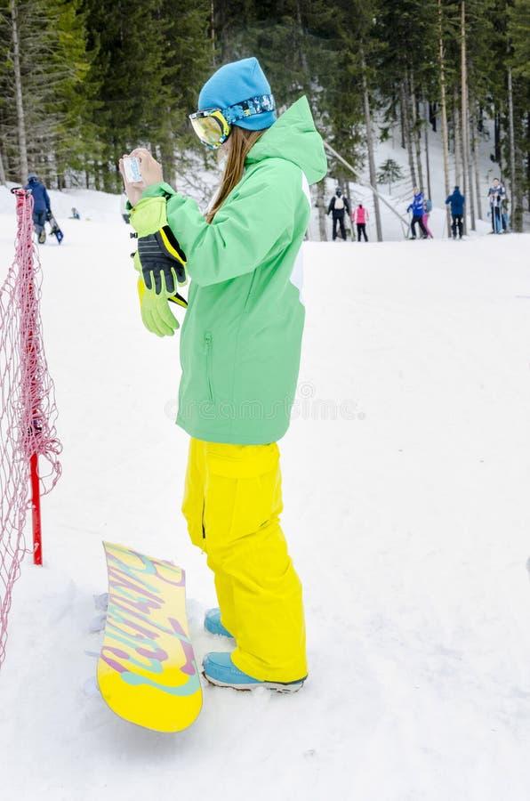 享受冬天假期的雪板女孩做照片 图库摄影