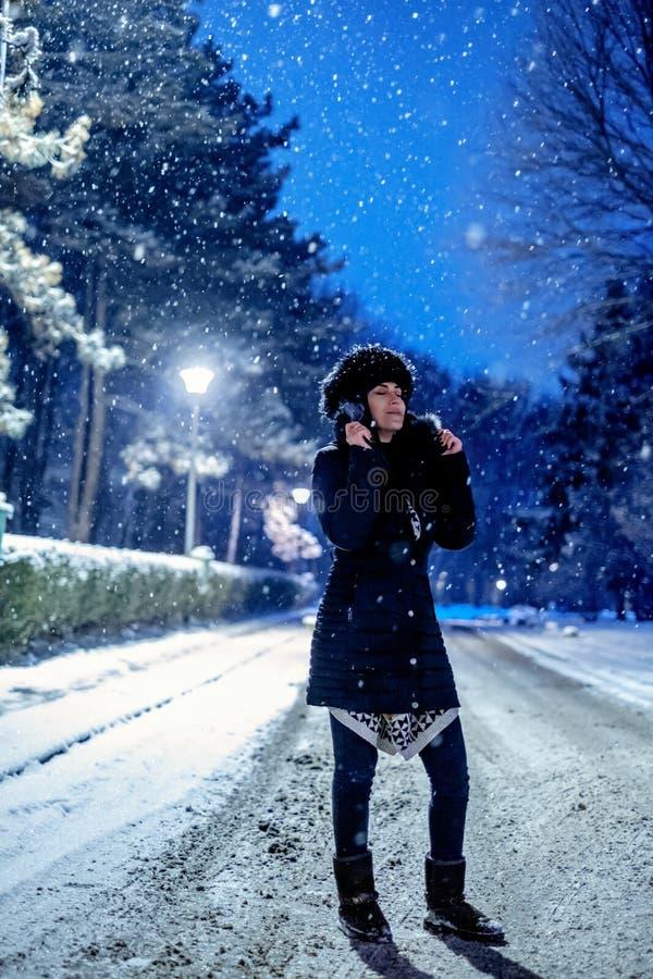 享受冬天晚上的女孩在公园 库存图片