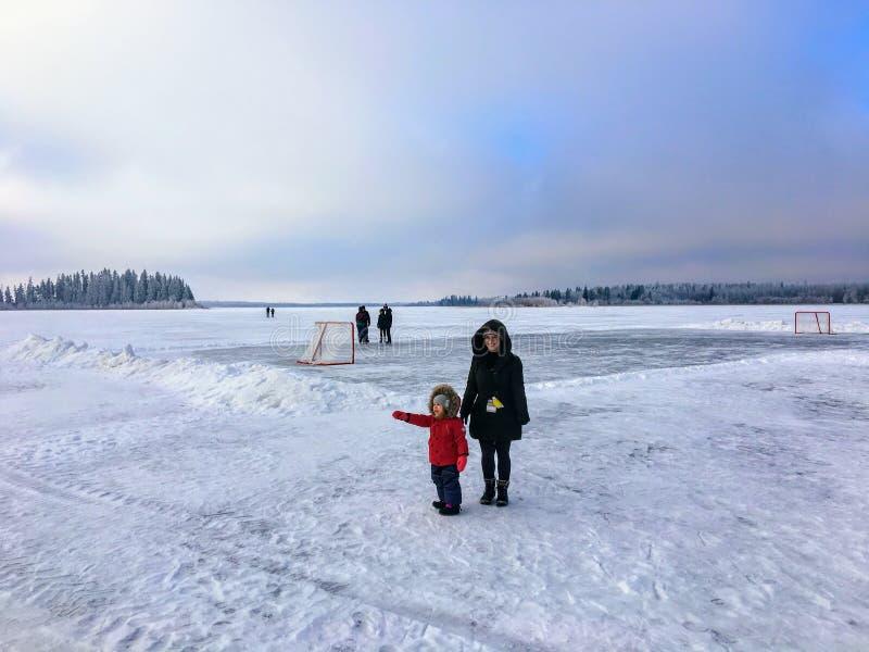 享受冬天的母亲和女儿通过走在Astotin湖冻湖  库存照片