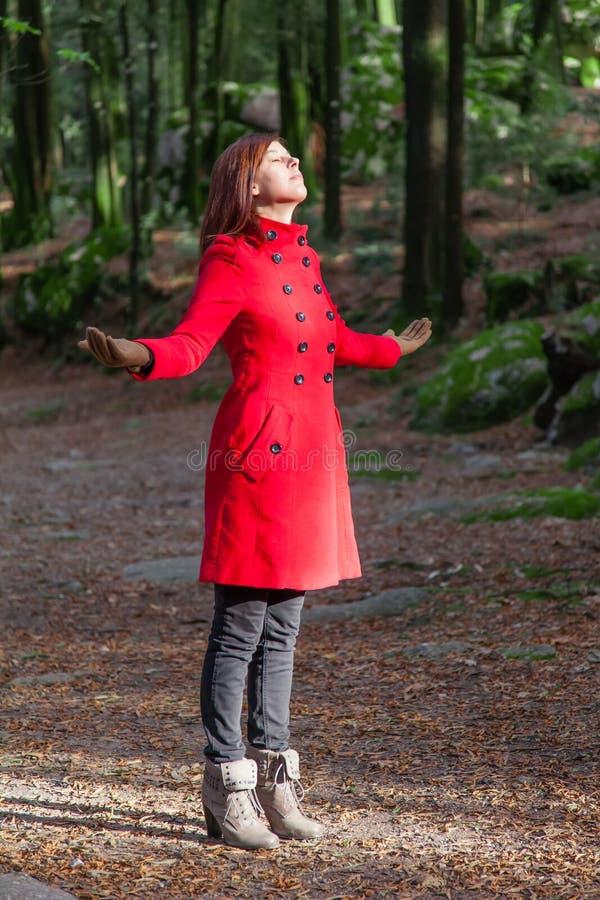 享受冬天阳光的温暖的在森林的妇女 免版税图库摄影