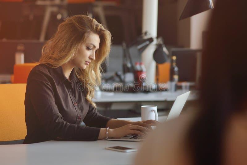 享受创造性的运作的过程的企业的快乐的雇主画象在现代办公室户内 免版税库存图片