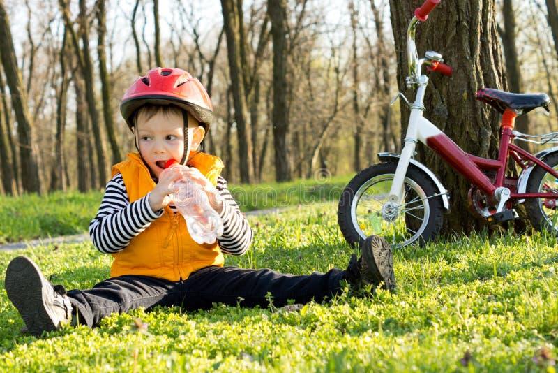 享受刷新的水的饮料年轻骑自行车者 库存图片