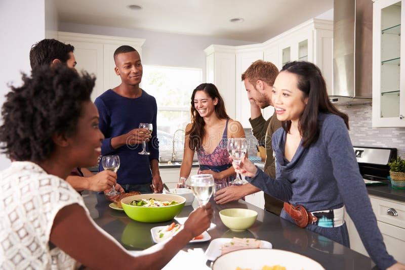 享受前晚餐的小组朋友在家喝 免版税图库摄影