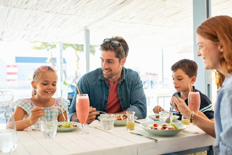 享受午餐的愉快的年轻家庭室外 免版税库存图片