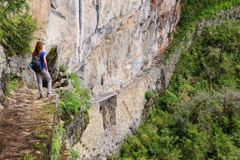 享受印加人桥梁和峭壁道路的看法少妇近 免版税库存照片