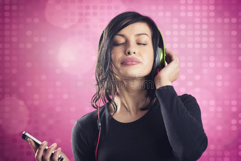 享受听到与耳机的音乐的愉快的镇静女孩 图库摄影