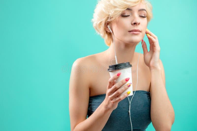 享受听到音乐的令人敬畏的白肤金发的女孩,当喝咖啡时 库存图片