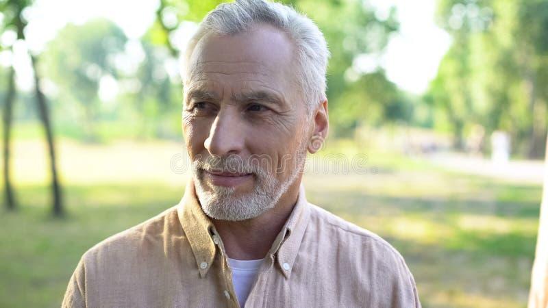 享受周末的英俊的灰发的人在公园,室外愉快的男性的领抚恤金者 免版税库存图片