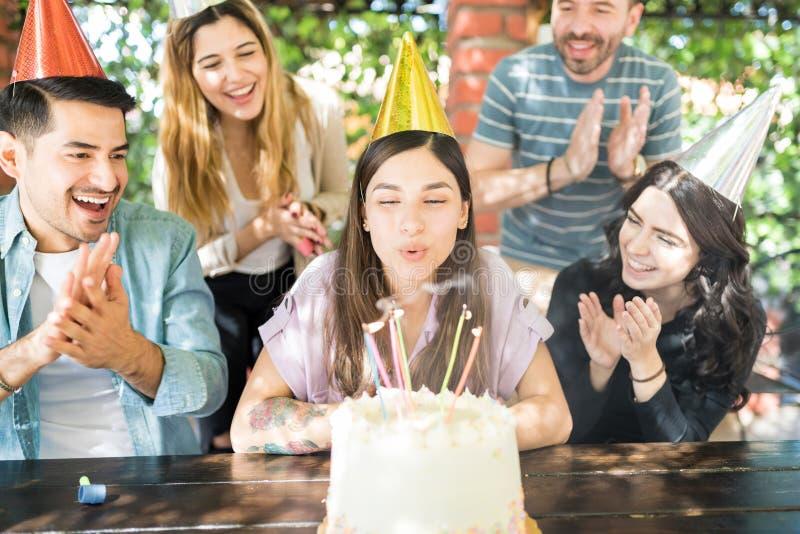 享受和庆祝生日的不同种族的朋友 免版税库存图片