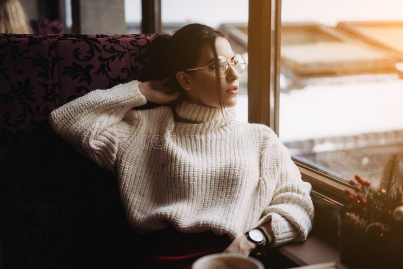 享受咖啡的味道女孩,当放松在咖啡店时 免版税库存照片