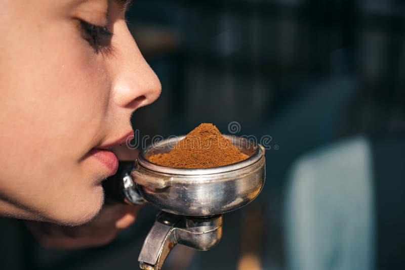享受咖啡芬芳和芳香 妇女嗅新鲜的碾碎的咖啡的气味 妇女barista举行portafilter 免版税库存照片