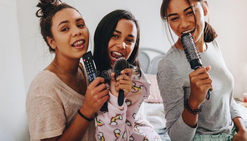 享受唱歌的三个女孩在sleepover 免版税库存图片
