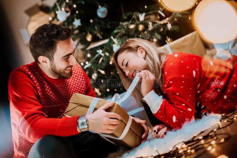 享受圣诞节和打开礼物或礼物的完善的夫妇 免版税库存照片