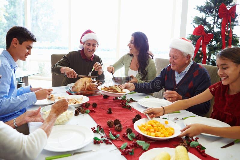 享受圣诞节膳食的多一代家庭在 免版税库存图片